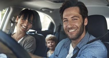 A mother, father, and a child sitting in a car, smiling