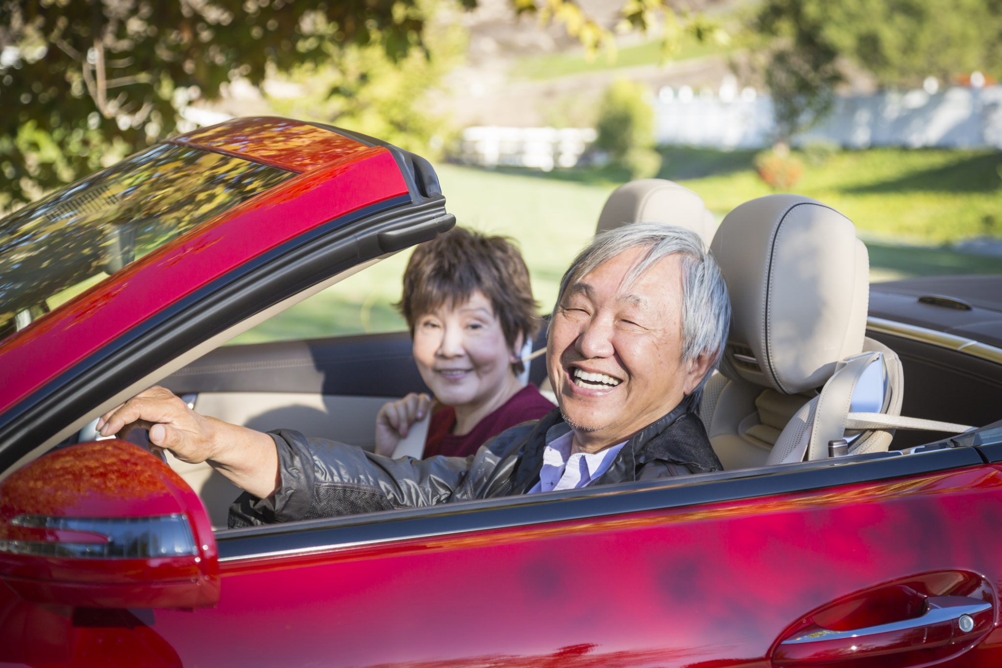 Attractive Happy Couple Enjoying An Afternoon Drive in Their Convertible.